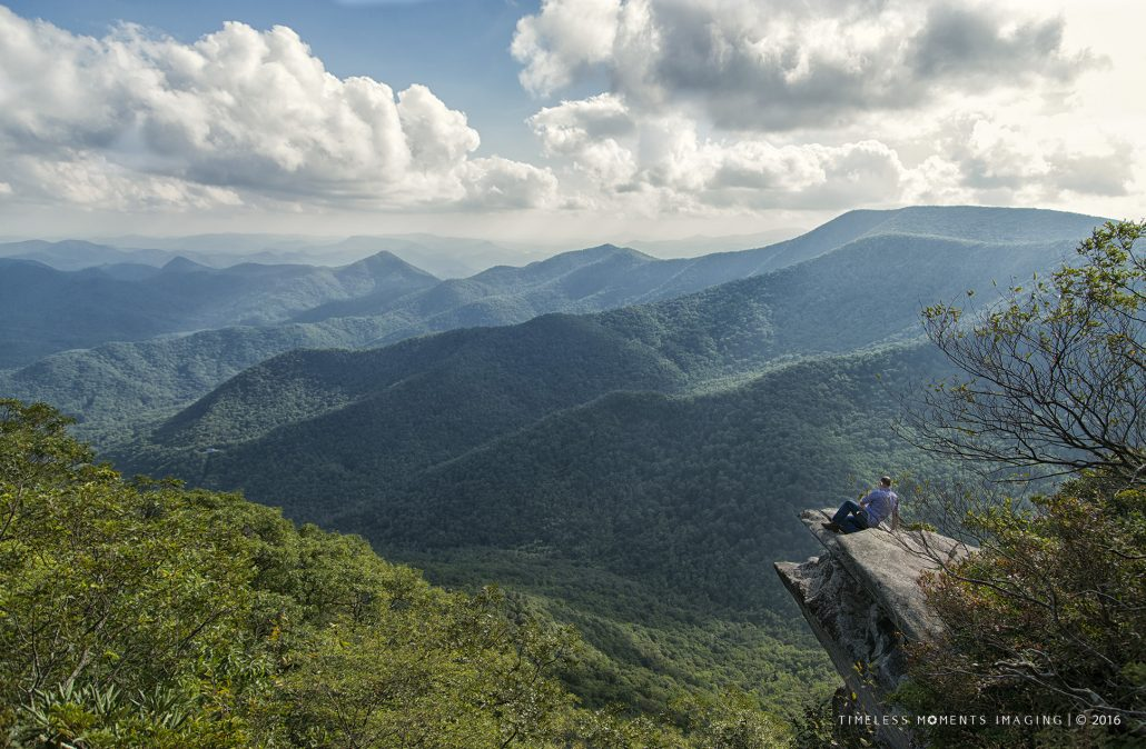 A hiker relaxes and takes in the view from Pickens Nose